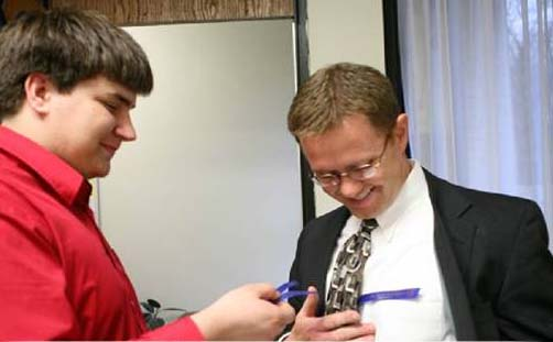 Student Handing ribbon to executive