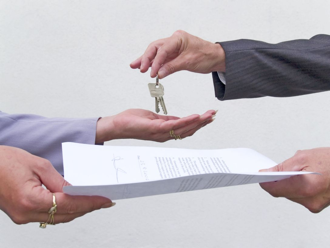 Hands exchanging contract for a set of house keys.